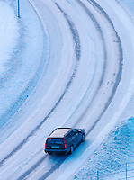 A car drives slowly through the frozen streets of Tromso, Norway