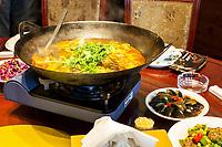 Nanjing, Jiangsu, China.  Heating Fish Heads and Tofu Soup, Cured Eggs on Side.