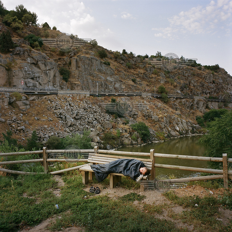 A young man rests on a bench inside his sleeping bag beside the river Tajo...