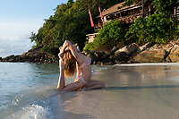 Girl practicing yoga pigeon pose in rolling waves. Ko Lipe island, Thailand