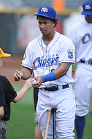 Cheslor Cutbert #24 of the Omaha Storm Chasers autographs ball for a young friend prior to their game against the Las Vegas 51s at Werner Park on August 17, 2014 in Omaha, Nebraska. The Storm Chasers  won 4-0.   (Dennis Hubbard/Four Seam Images)