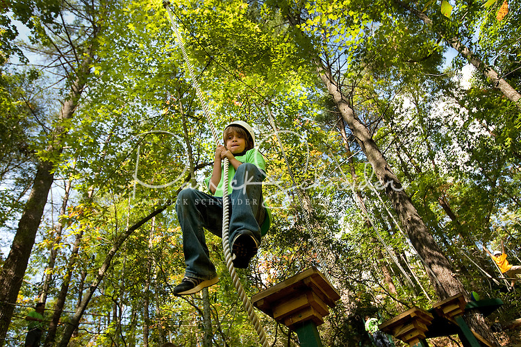 A young man hangs onto a rope to jump between wooden platforms on a ropes obstacle course at a camp in the North Carolina Blue Ridge Mountains. Boy is a cub scout who is wearing his Class B uniform. The ropes course was designed to spur confidence through this challenging outdoor activity.