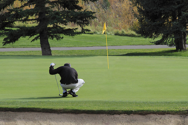 Man putting at the Vail Golf Course, Vail Colorado, USA.