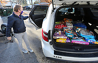 Adam Roberts, project coordinator with city of Fayetteville Community Resources, loads pet food Tuesday, January 5, 2021, into a vehicle for distribution from the AniMeals facet of the Ranger's Pantry at the pet food pantry in Fayetteville. AniMeals provides food directly to pet owners who have applied through the Meals on Wheels program. The pet food bank is a project of the Community Resources Division and is available to families that live in the city of Fayetteville. Information on the food bank and to receive vouchers can be found here: fayetteville-ar.gov Check out nwaonline.com/210106Daily/ and nwadg.com/photos for a photo gallery.<br /> (NWA Democrat-Gazette/David Gottschalk)