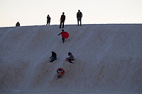 People slide down sand dunes at White Sands National Monument near Alamogordo, New Mexico, USA, on Sat., Dec. 30, 2017.