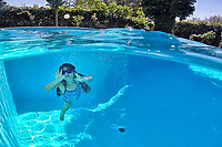 Υoung girl swims at the pool on half underwater view