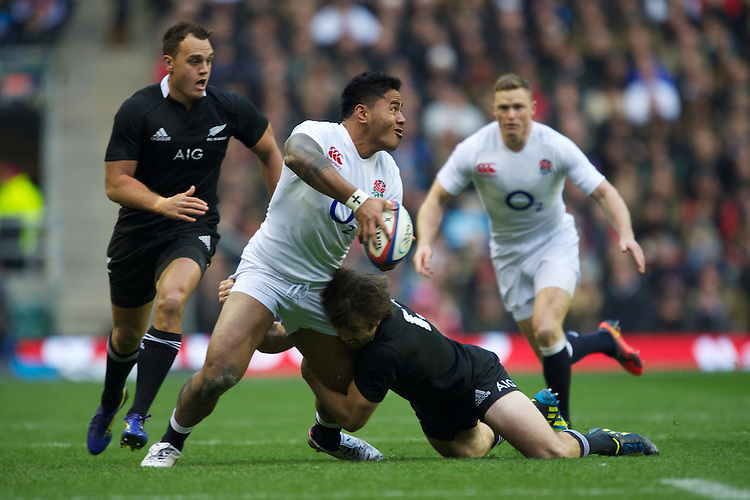 Manu Tuilagi of England iooffloads as he is tackled by Conrad Smith of New Zealand during the QBE Autumn International match between England and New Zealand at Twickenham on Saturday 01 December 2012 (Photo by Rob Munro)