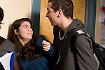 Education High School public male and female student interacting in corridor between classes