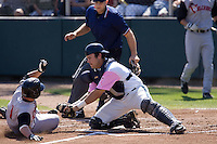 August 30, 2009: Everett AquaSox catcher Trevor Coleman blocks the plate as Salem-Keizer Volcanoes' Joel Weeks attempts to score during a Northwest League game at Everett Memorial Stadium in Everett, Washington.  The AquaSox wore pink jerseys for breast cancer awareness.