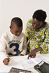 Nine year old boy at home working on homework, math assignment, assisted by mother