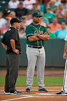 Greensboro Grasshoppers manager Miguel Perez (29) during the lineup exchange, including umpire Rene Gallegos, before a South Atlantic League game against the Delmarva Shorebirds on August 21, 2019 at Arthur W. Perdue Stadium in Salisbury, Maryland.  Delmarva defeated Greensboro 1-0.  (Mike Janes/Four Seam Images)