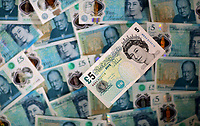 An old £5 note resting on a bed of new ones<br />