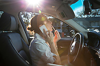 A businesswoman applies lipstick mascara and talks on her smart phone while driving in downtown residential Austin traffic.