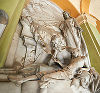 Pictures of the stone sculpture of a father and son in realistic style being handed a will by the deceased. Tomb of Gian Battista Castagnola 1896. The monumental tombs of the Staglieno Monumental Cemetery, Genoa, Italy
