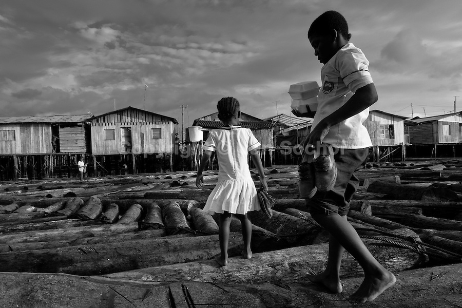 Displaced children walk over the wooden logs in the stilt house area in Tumaco, Nariño dept., Colombia, 12 June 2010. With nearly fifty years of armed conflict, Colombia has the highest number of civil war refugees in the world. During the last ten years of the civil war more than 3 million people have been forced to abandon their lands and to leave their homes due to the violence. Internally displaced people (IDPs) come from remote rural areas, where most of the clashes between leftist guerrillas FARC-ELN, right-wing paramilitary groups and government forces takes place. Displaced persons flee in a hurry, carrying just personal belongings, and thus they inevitably end up in large slums of the big cities, with no hope for the future.