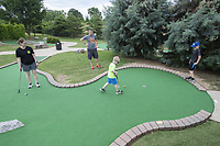 Cade Nelson, 5, makes his putt Monday June 7, 2021 while playing miniature golf with his parents Megan Nelson (from the left) and Scott Nelson of Lawrence Kansas and his brother Drake Nelson, 10. The family was in the area for Scott Nelson to compete in a triathlon. They were playing at Golf Mountain Mini Golf in Rogers. For information see https://golf-mountain.net/ Visit nwaonline.com/2100608Daily/ and nwadg.com/photo. (NWA Democrat-Gazette/J.T. Wampler)