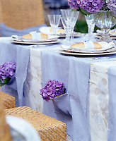 Fabric overlays with pockets have been laid at each place setting and filled with an Hydrangea flower for each guest