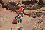 Father pulling his children in wagons on a trail in Arches National Park, Moab, Utah, USA. .  John offers private photo tours in Arches National Park and throughout Utah and Colorado. Year-round.