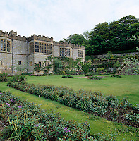 The castellated stone facade of Haddon Hall with the leaded mullion windows of the Long Gallery that look out over the garden
