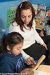 Afterschool homework help program for Headstart graduates Grades K-3 female teacher working with first or second grade student, using abacus