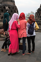 Borobudur, Java, Indonesia.  Indonesian Woman on Right Holds Camera on an Extender Pole to Take a Selfie of Herself and Friends Visiting the Temple.