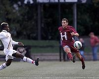 Harvard University defender Ross Friedman (4) passes the ball. Boston College (white) defeated Harvard University (crimson), 3-2, at Newton Campus Field, on October 22, 2013.