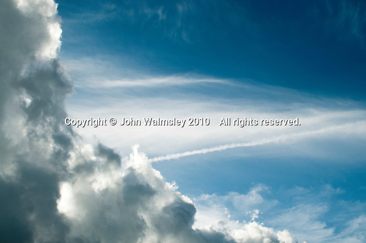 Cumulus clouds, an aircraft's contrail and high beyond everything, cirrus clouds.
