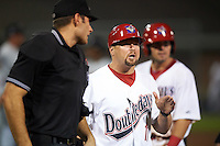 Auburn Doubledays manager Jerad Head (11) argues a call at first with umpire Louie Krupa (not shown) as home plate umpire Dane Ponczak steps in during a game against the Tri-City ValleyCats on August 25, 2016 at Falcon Park in Auburn, New York.  Tri-City defeated Auburn 4-3.  (Mike Janes/Four Seam Images)