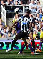 Pictured: Jordi Amat of Swansea (L) challenged for a header by Shola Ameobi of Newcastle. Saturday 19 April 2014<br /> Re: Barclay's Premier League, Newcastle United v Swansea City FC at St James Park, Newcastle, UK.