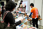 """A woman reads an anime book at the  the Niconico Douga fan event at Makuhari Messe International Exhibition Hall on April 25, 2015, Chiba, Japan. The event includes special attractions such as J-pop concerts, Sumo and Pro Wrestling matches, cosplay and manga and various robot performances and is broadcast live on via the video-sharing site. Niconico Douga (in English """"Smiley, Smiley Video"""") is one of Japan's biggest video community sites where users can upload, view, share videos and write comments directly in real time, creating a sense of a shared watching. According to the organizers more than 200,000 viewers for two days will see the event by internet. The popular event is held in all 11 halls of the huge Makuhari Messe exhibition center from April 25 to 26. (Photo by Rodrigo Reyes Marin/AFLO)"""