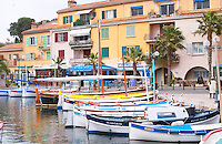 View of the harbour with fishing and leisure boats and sea front buildings Typical Provencal fishing boats painted in bright colours white, blue, green red yellow, moored at the keyside Sanary Var Cote d'Azur France