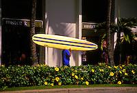 Carrying a surfboard past upscale shops on Kalakaua Ave., Waikiki, Oahu