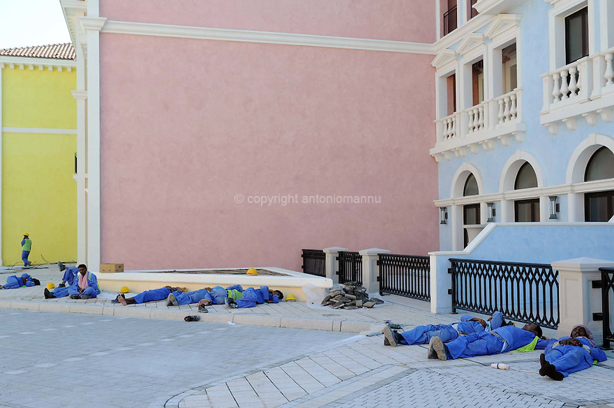 Doha Qatar novembre 2010. Operai in pausa durante la costruzione dello sviluppo immobiliare The Pearl. Una parte è liberamente ispirata all'architettura di Venezia. Workers at rest during the construction works of the new real estate development The Pearl a part of which is freely inspired  by Venezia's architecture.