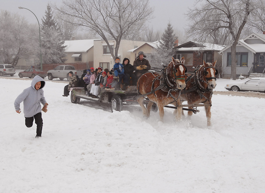A boy races a horse and sleigh team during a community Christmas celebration in North Central. MARK TAYLOR GALLERY