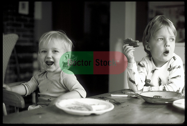 young boy and girl laughing and eating breakfast