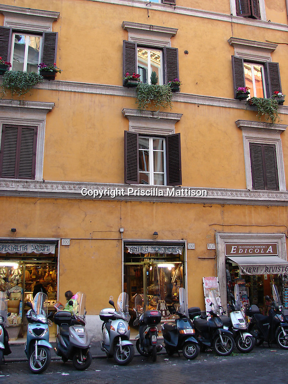 Rome, Italy - January 29, 2007:  Scooters are lined up at the base of a building.
