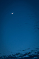 The waxing crescent moon, like a sleepy eye, looks down on scattered clouds over the western horizon.