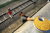 A hawker selling chickpeas climbs aboard teh roof of a train. In Bangladesh many people ride on the roofs of trains as frequently that is the only space available. For others, the fares are too high and can be avoided or reduced by travelling on the roof. This practice has led to many hawkers plying their trade on train roofs too. However, riding on roofs and other parts of train exteriors leads to regular accidents, many of them fatal..