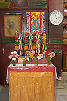 Bodhnath, Nepal.  A Table inside the Tsamchen Gompa (Monastery).  A Thangka (Tibetan Buddhist Painting) hangs on the wall.