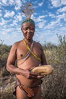 Africa, Botswana, Khwai, The Lodge, Feline Fields, edge of the Kalahari desert. Kalahari bush people, Ju'hoansi tribe. Hunter-gatherer !Kung people, part of San tribe. Although they are no longer legally allowed to hunt, the tribe shows how they use their bow and arrow and make guineau fowl traps. The also show how they gather different berries and herbs for eating and using as insect repellent. The elder tribesman still know how to find the large tubers (Qhgwaa) that they dig up to drink from for hydration. In the rainy season they use ostrich shells to store water. They also can still make fire by rubbing sticks together. Tribal shaman.