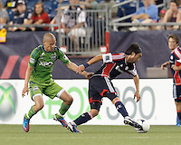 New England Revolution midfielder Lee Nguyen (24) dribbles as Seattle Sounders FC midfielder Osvaldo Alonso (6) defends. In a Major League Soccer (MLS) match, the New England Revolution tied the Seattle Sounders FC, 2-2, at Gillette Stadium on June 30, 2012.