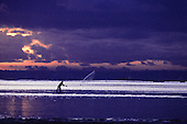 Bahia, Brazil. Fisherman throwing his net from the beach at dawn.