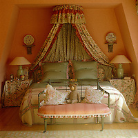 This feminine bedroom is decorated in a combination of pretty pastel chintzes