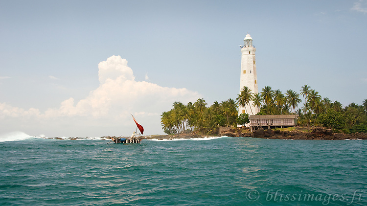 A fisherman in his outrigger canoe lets his sail fly by Dondra Lighthouse, Sri Lanka.