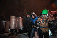 Protesters fee from the assault of the police during the  nightly evacuation  of the  government district in Kiev. Ukraine
