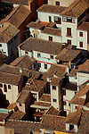 Spain, Grenada, Rooftops, Andalucia, A composition of sunlit stucco houses with red tiled rooftops viewed from above..
