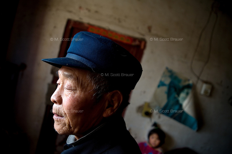 Fan Xi Bao stands inside his home in Fanzhuang Village, Gangyun County, Jiangsu, China, where he and wife Wang Shou Ha care for their orphaned granddaughter Fan Li Na, 10.  The girl's father died in a car crash in 2000 and the girl's mother remarried, abandoning the girl.  Both grandparents are over 60 and have health problems which make it impossible to support the girl if she continues school.  ..At the time of the picture, China's Amity Foundation charity, was investigating the family's situation in preparation to raise money to financially support these children and other orphans in similar situations.  With Amity's support, each orphan, aged 6-12, would receive approximately 1,400 RMB annually (about 200 USD) to pay for the cost of living. Amity works to keep children out of the institutional orphanages in China, preferring to provide monetary assistance that can help maintain a family environment for the orphans it helps.