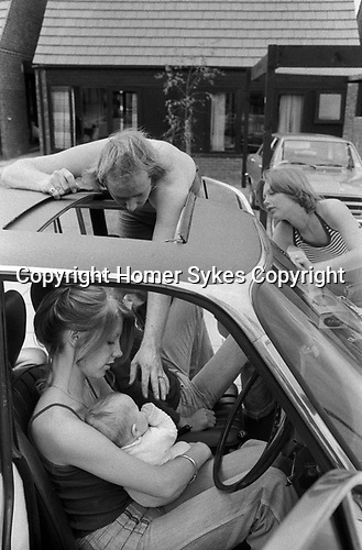 1970s professional middle class couple outside their new modern home on a new housing development. Father going to touch his new baby, mother looking on. Baby being held by girlfriend who is up for the day to see the new house and baby. Hanging out by the family car that is parked out side their house. 1977. Milton Keynes Buckinghamshire.