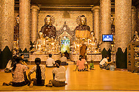 Myanmar, Burma.  Shwedagon Pagoda, Yangon, Rangoon.  Evening Lights Illuminate  Worshipers Praying in a Buddhist Shrine.