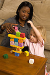 Child care provider babysitting playing with balancing game with 3 year old girl